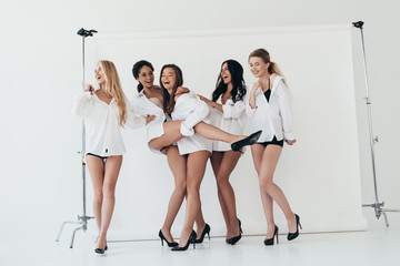full length view of sexy multiethnic feminists wearing heels and white shirts laughing on white