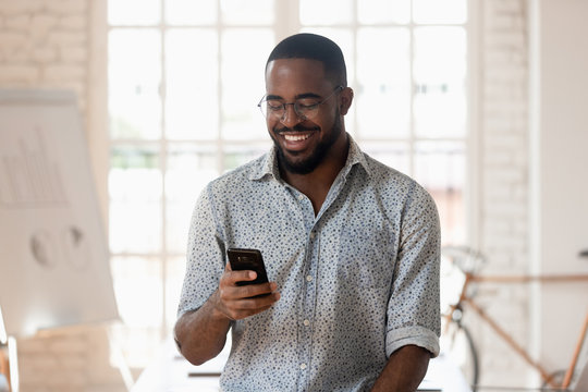 Happy black businessman holding smartphone using apps standing in office