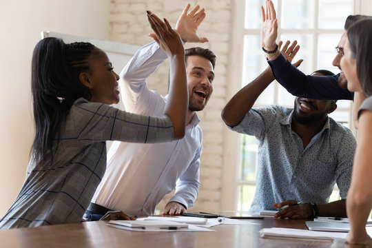 Multiracial euphoric business team people give high five in office