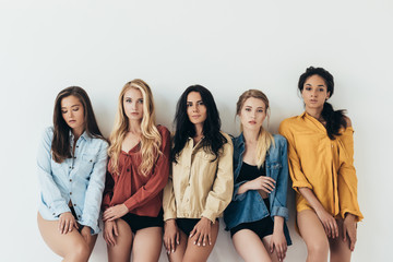 front view of five sexy multiethnic feminists in colorful shirts looking at camera isolated on grey