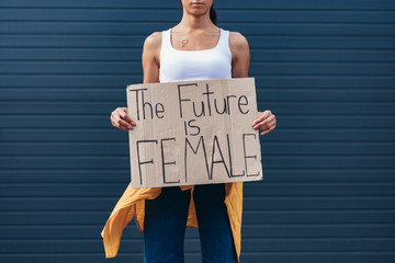 cropped view of feminist holding placard with inscription the future is female