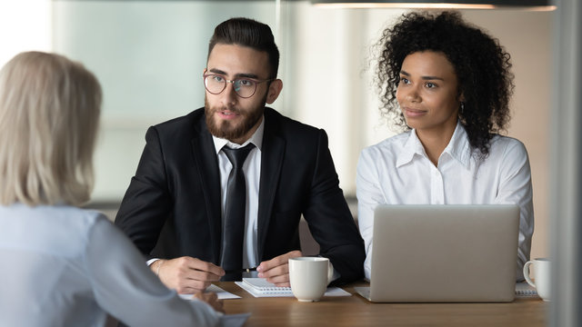 Two diverse hr managers holding job interview with mature applicant