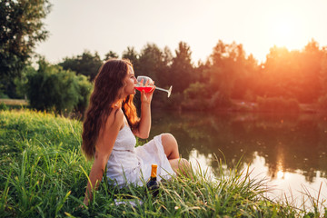Young woman enjoying glass of wine on river bank at sunset. Woman admiring landscape while having drink Wall mural