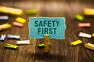 Word writing text Safety First. Business concept for Avoid any unnecessary risk Live Safely Be Careful Pay attention Clothespin holding blue paper note reminder clothespins wooden floor