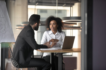 African American businesswoman consulting client in boardroom