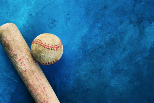 Old baseball bat with ball on blue texture background for sport graphic.  Copy space beside vintage sports equipment.