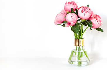 Peony flower bouquet in a vase on the white background close up frame. Copy space