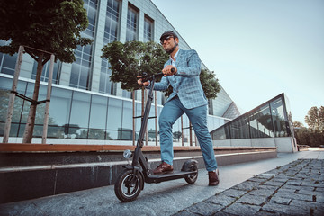 Low angle photo of smart elegant man in sunglasses and helmet which is driving his electrical...