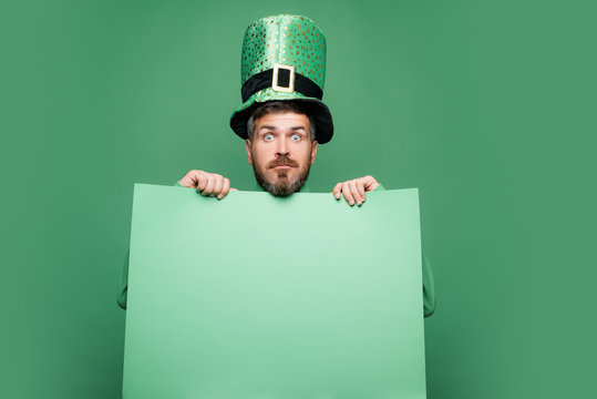Shocked and happy male face. Happy Saint Patrick's day. Hipster in leprechaun hat and costume with wide open eyes celebrating Saint Patrick's day.