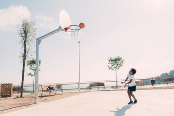 Black boy playing basketball at the park in the morning. Horizontal photo