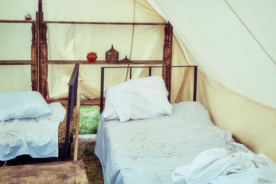 Bed under a large tent retro field hospital. Military field medicine in the 18th or 19th century. Portable hospital for wounded soldiers.
