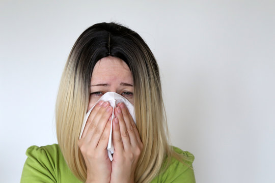 Sick woman sneezing and blowing her nose in a handkerchief. Concept of colds and flu, runny nose, airborne infection