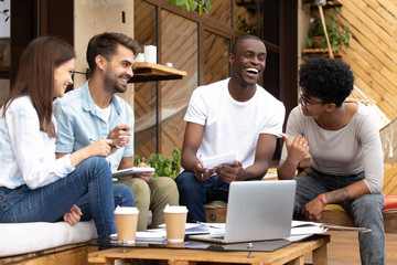 Smiling diverse millennial friends have fun studying in cafe Wall mural
