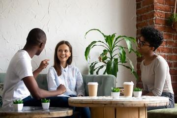 Smiling multiracial friends talk have fun in coffeeshop