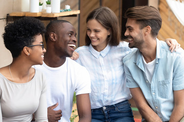 Portrait of happy diverse millennial friends hug at meeting