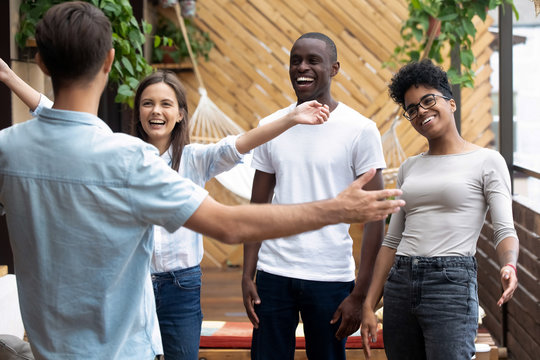 Happy multiracial friends feel excited meeting friend in cafe