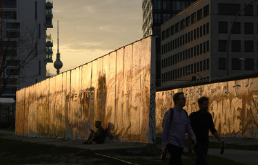 People visit the open air East Side Gallery close to river Spree in Berlin