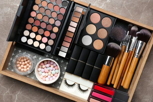 Set of different professional makeup products in box on table, top view