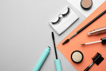 Flat lay composition with false eyelashes and other makeup products on color background, space for text