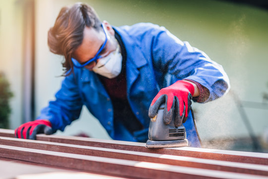 Young good looking handyman wearing protective mask and glasses. Man grinding old window surface with electric grinder and abrasive paper. Men housework concept.