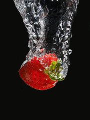 Strawberries in the water on black background