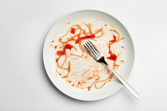 Dirty plate with food leftovers and fork on white background, top view