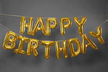 Phrase HAPPY BIRTHDAY made of golden balloon letters on grey background