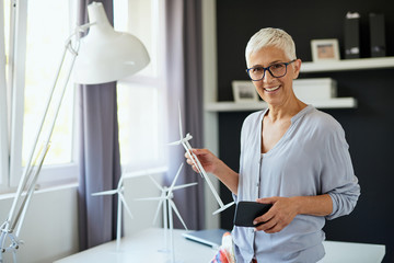 Beautiful smiling Caucasian senior woman standing in office, holding windmill model and smart...