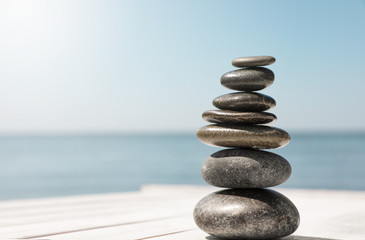 Obraz Stack of stones on wooden pier near sea, space for text. Zen concept - fototapety do salonu