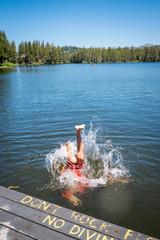 Boy jumping into beautiful blue lake