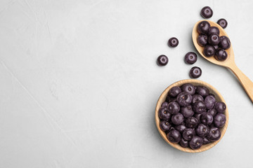 Flat lay composition with fresh acai berries on light stone table, space for text