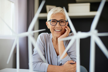 Happy Caucasian senior woman leaning on desk and looking at camera. On desk are windmill models. Start up business concept.