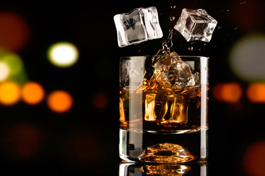 glass of whiskey and ice cube