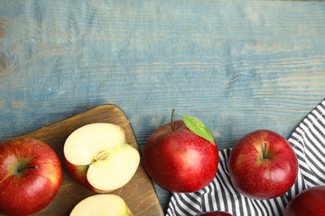 Ripe juicy red apples on blue wooden background, flat lay. Space for text Wall mural
