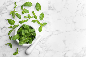 Fresh mint with mortar and pestle on white marble background, flat lay. Space for text