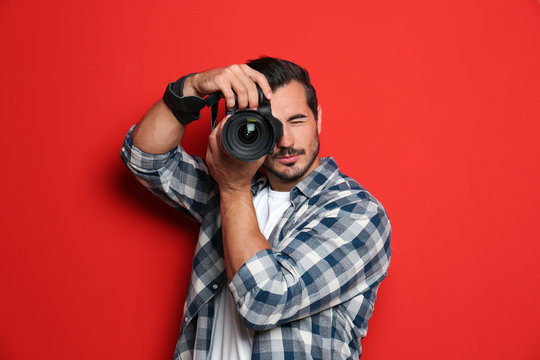 Young professional photographer taking picture on red background