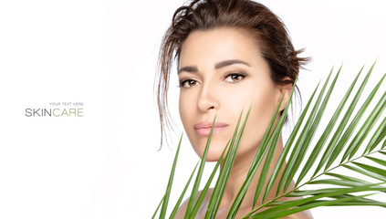 Beautiful young woman with green tropical leaf. Spa, skincare and wellness concept