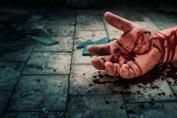 Crime scene with human hand in blood on floor of killed man by murder, dead body part close up - fototapety na wymiar
