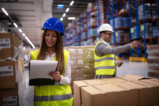 Female factory worker in reflective uniform with hardhat helmet checking new arrival of goods in warehouse while worker using bar code reader in background. Logistics and distribution.