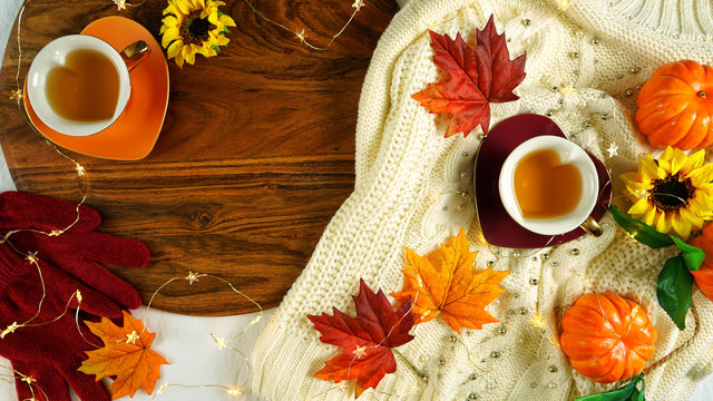Autumn Fall theme flatlay overhead with cosy sweater, bagels, cups of herbal tea and scattered maple leaves.