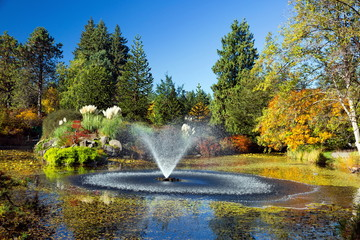Pond with fountain in Van Dusen Park,  sunny  autumn day Rainbow in Fountain  colorful view, green and yellow trees on the background of blue sky