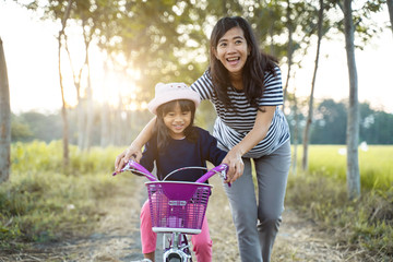 mom teach her toddler daughter to learn bicycle outdoor