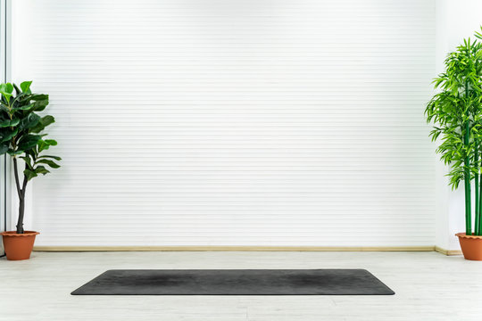 Empty room with yoga mat on floor with white wall. Can use for backdrop and background.