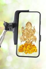 Selfie stick with smartphone isolated with hindu god ganesha