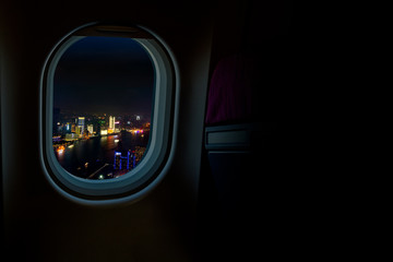 Night cityscapes view from airplane window in the sky with dark copy space for text