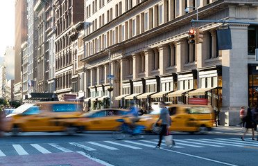 Yellow taxis in motion on 5th Avenue through Midtown Manhattan New York City