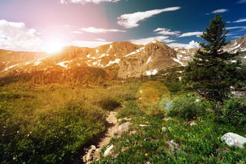 Sunset light shining behind a distant mountain range and a dirt hiking trail winding through an alpine meadow in Colorado