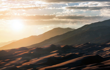 Sunlight shining over Great Sand Dunes National Park in the Colorado Rocky Mountains