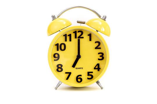 Yellow alarm clock on white at 7 o'clock