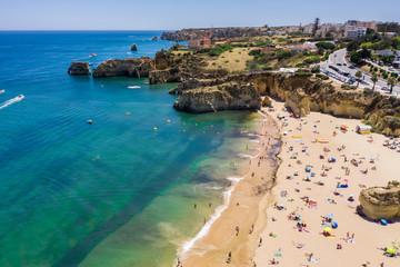 Tourists relaxing on Praia da Batata beach, Lagos, Algarve, Portugal, Europe, aerial drone wide view Wall mural